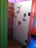 Walk -in shower with blue/green glass tile.