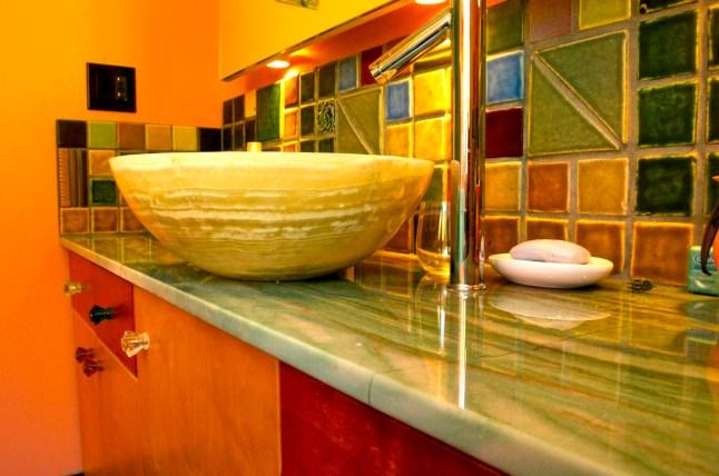 Green Onyx counter top with Onyx vessel sink. Pewabic tile backsplash.