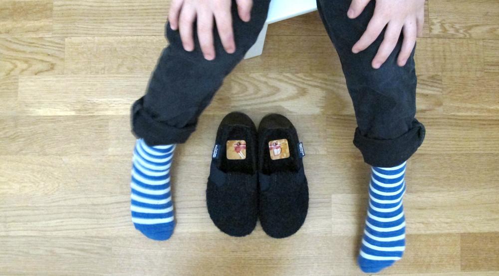 Beine Junge mit Hausschuhen und Laufkleber