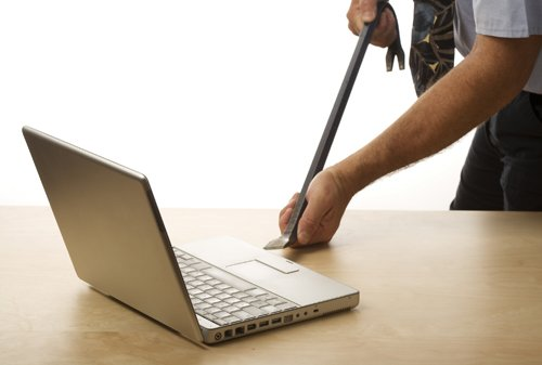 Technician opening a laptop with a crowbar.