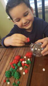 Little boy making diy handmade ornament using pom poms