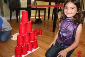 little girl stacking red solo cups into a pyramid
