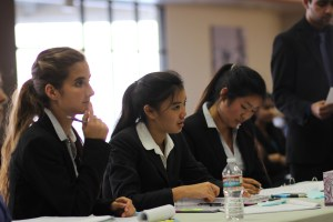 Mock Trial attorney Erika DePalatis, Yuan Tao and Gina Sakoda take notes during a cross-examination in a scrimmage against Moreau Catholic.