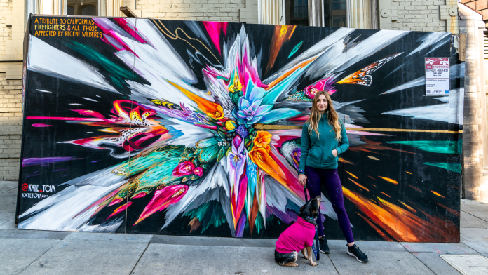 Kate Tova poses in front of her artwok with her rescue dog, Toochi