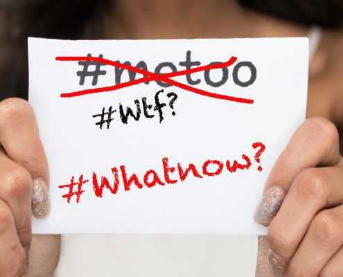 "Girl holding up small note card that reads ""Its not about #metoo;its about #whatnow"