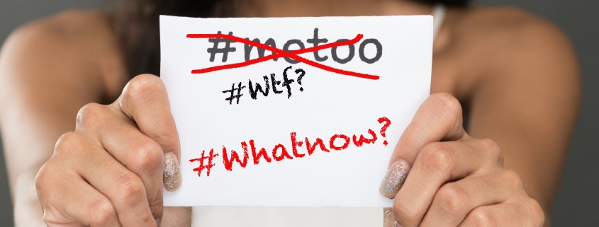 """Girl holding up small note card that reads """"Its not about #metoo;its about #whatnow"""