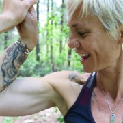 Strong, tattooed woman flexing her bicep