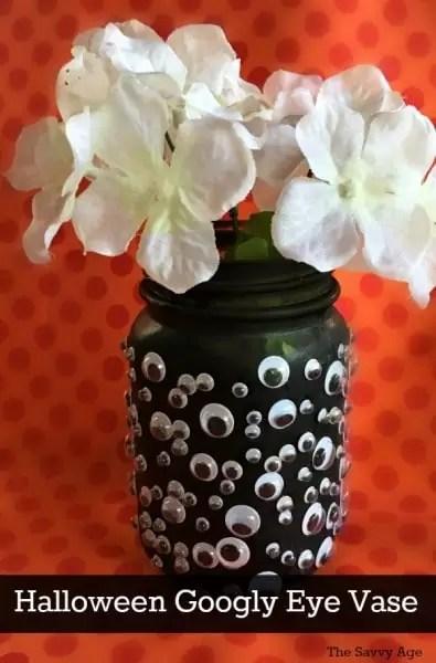 Googly eye vase with white flowers.
