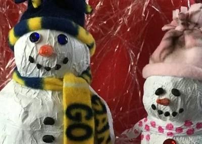 Two paper mache snowmen heads.