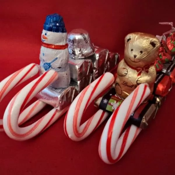 Two candy cane sleighs with chocolate presents and teddy bear driver.