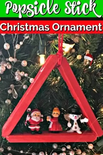 Popsicle stick christmas ornament decorated with mini santa.