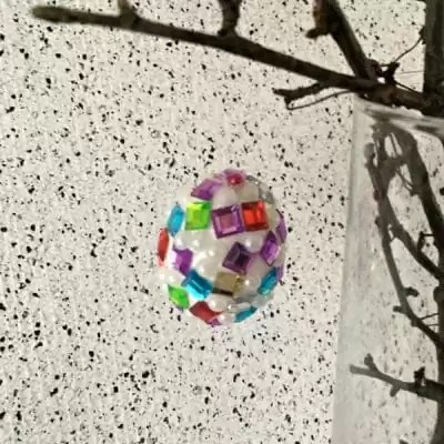 easter egg covered in jewels hanging from tree