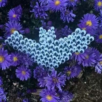 Bat filled with googly eyes in purple flowers