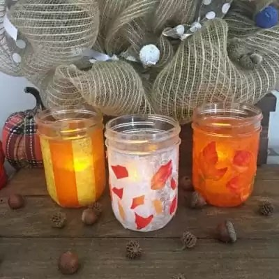 Mason jars decorated with leaves, orange and yellow stripes.