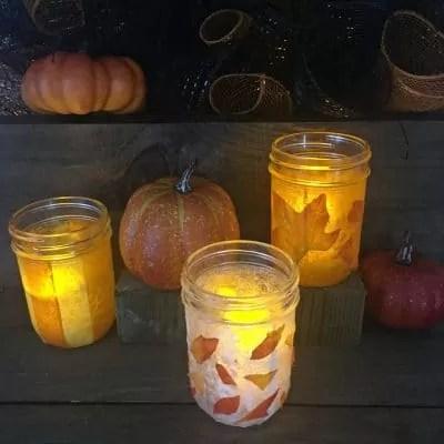 Three illuminated mason jars decorated with leaves.
