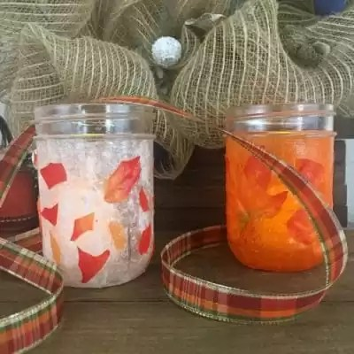 Two mason jars decorated with leaves.