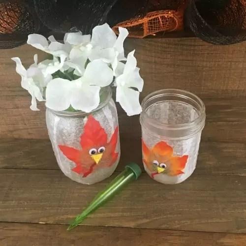 mason jar decorated with a turkey and fresh flowers.