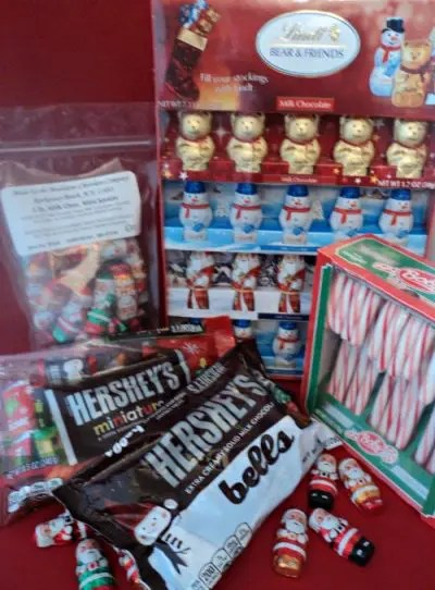 Assorted milk chocolate candy: mini candy bars, chocolate bells, mini santas and mini teddy bears Christmas red, white and green colors. Box of candy canes.