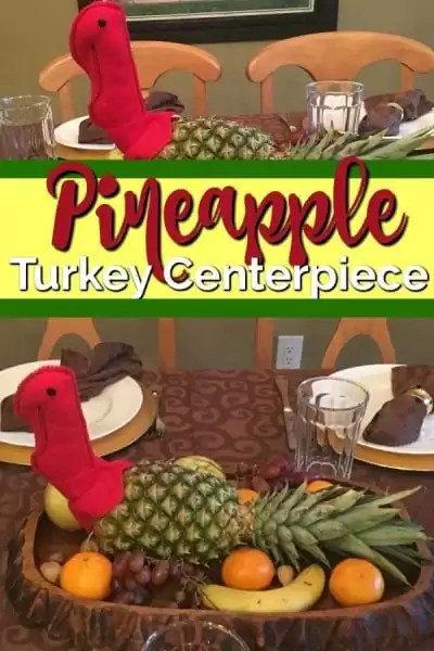 Turkey centerpiece made with a pineapple body and red turkey head surrounded by fresh fruit on a wood platter.