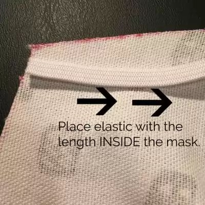 Inside of mask with white elastic laying flat.