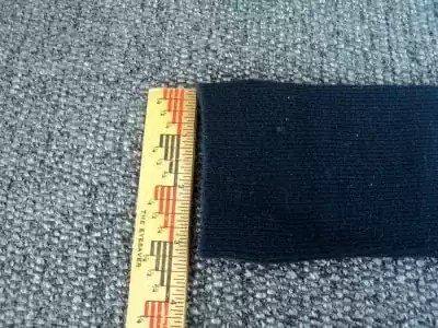 Black sock with top measured at 3 inches by a ruler.