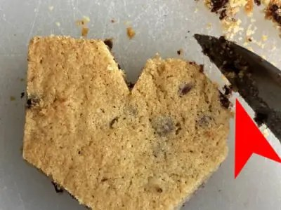 Chocolate chip cookies being shaved with knife into shape of a heart. Red arrow points to edge of top of heart.