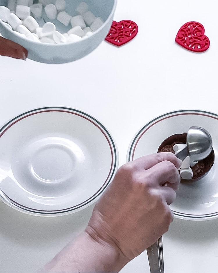Adding marshmallows to chocolate bomb half