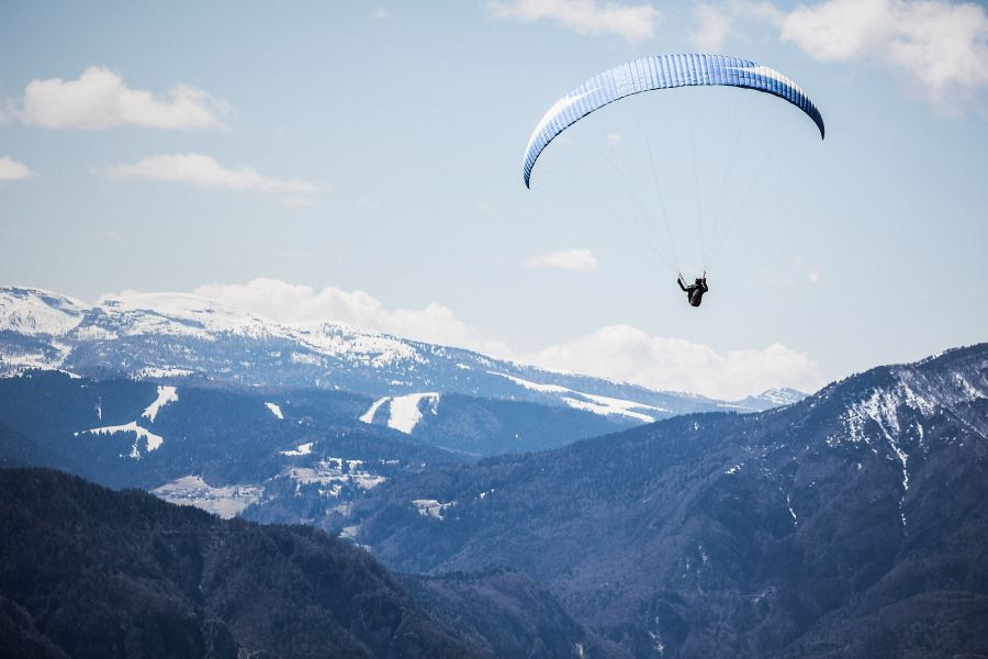 Photo by Vincentiu Solomon on Unsplash person on parachute over snow-capped mountains