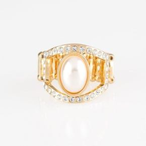 Large oblong pearl in the middle of a gold ring with rhinestones at top and bottom in gold actual ring is in silver
