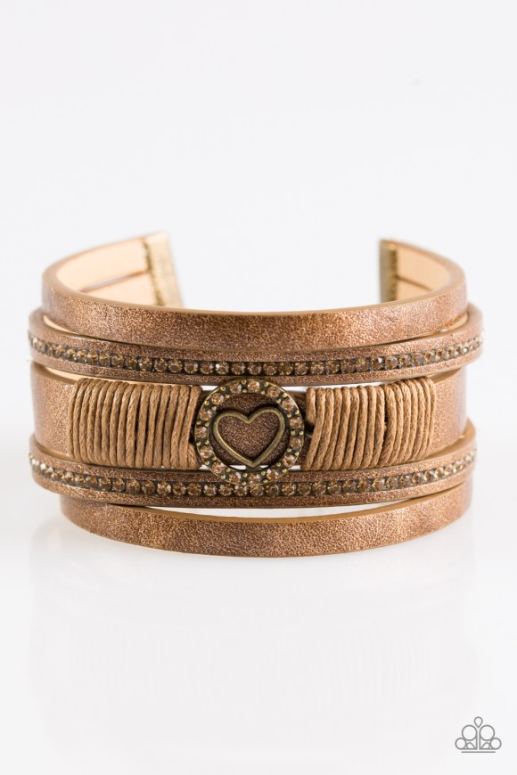Brushed in a metallic shimmer, strips of brown leather are encrusted in alternating rows of glittery topaz rhinestones. Brown cording knots around the centermost strand, securing a sparkling heart frame in place for a whimsical finish. Features an adjustable clasp closure. Sold as one individual bracelet.