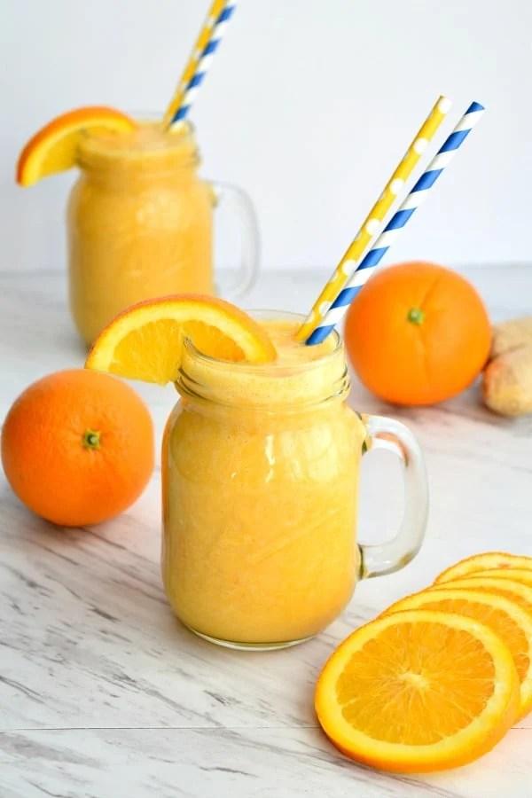 orange ginger smoothie with orange wedges and straws