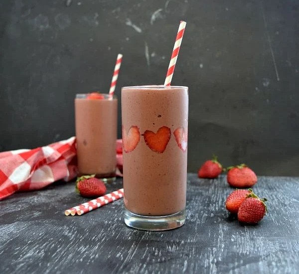 square image of 2 strawberry chocolate smoothies, strawberries stuck like hearts in the side of the smoothie