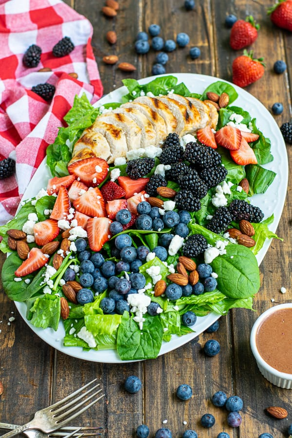 a platter full of mixed berry salad on a table with strawberry balsamic vinaigrette