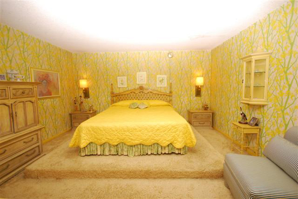 Bedroom with wallpaper with green branches and yellow leaves.