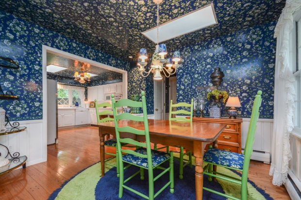 Dining room with walls and ceiling covered in navy wallpaper with bright green flowers.