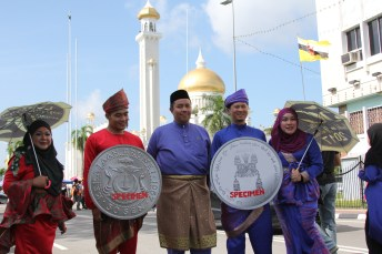 Men carrying mock-up of the special issue commemorative coins in conjunction with His Majesty's Golden Jubilee taking photos with members of the public. Photo: Ubaidillah Masli