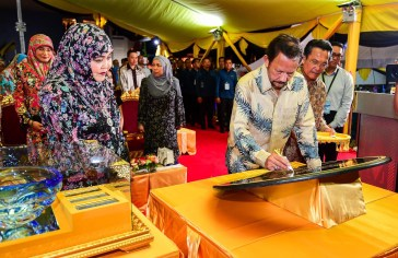 His Majesty (2R) signs a plaque during the launch of the RIPAS bridge, while Her Majesty (L) looks on. Photo: Infofoto