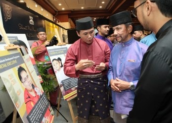 HM the Sultan is briefed by a Brunei Shell marketing employee during an exhibition at BSM's exhibition set up at Hari Raya celebration organised by Yayasan Sultan Haji Hassanal Bolkiah. Photo: Infofoto