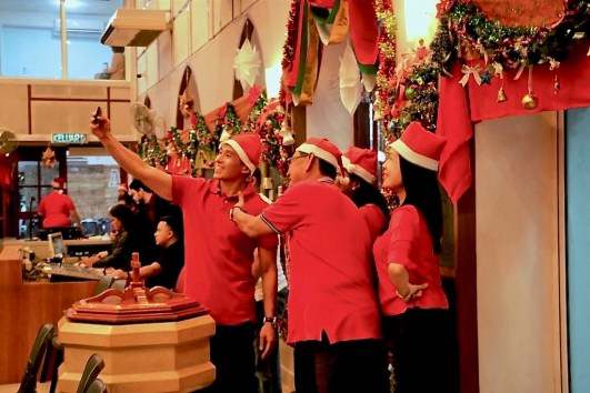 Church-goers dressed in Santa hats celebrate attend a Christmas Eve service at St Andrew's Anglican Church in Bandar Seri Begawan. Photo: Wardi Wasil/The Scoop