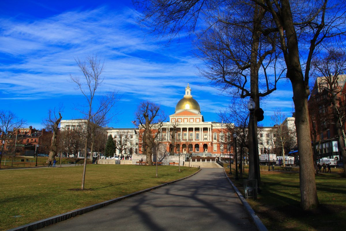 this photo shows the massachusetts state capitol building on beacon hill, taken from a distance in boston common