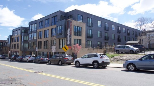 this image shows a street view of a large new condo development in Mission Hill, with cars parked in front.