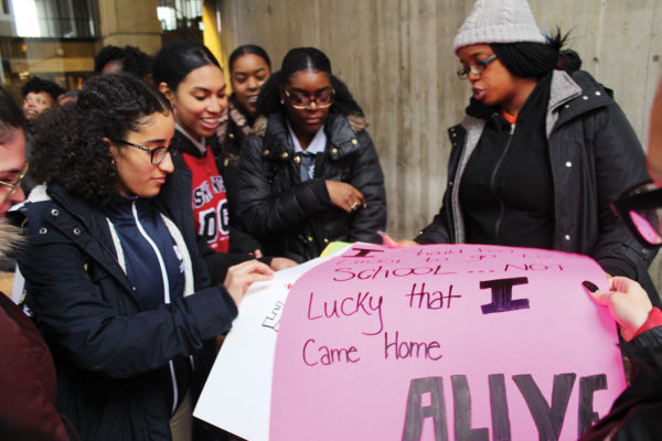"""Monica Cannon-Grant hands out posters to students outside City Hall at """"Die-in protest"""" in November 2018. Photo by Catherine McGloin."""