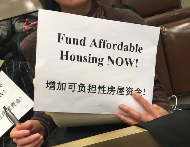 """Silent protestors in the crowd held signs that said """"Fund Affordable Housing NOW!"""" Photo by Joseph Handel."""