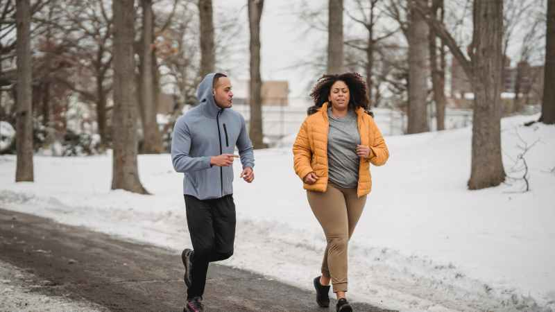 plump black woman running with trainer in winter park