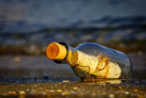 a corked bottle with a scroll inside it, lying on the ground near a body of water