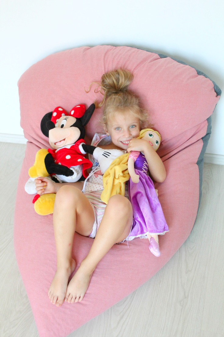 Little girl with dolls sitting on a DIY bean bag chair