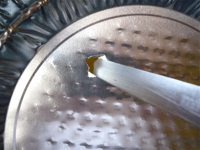 Use the tip of a sharp knife to pierce the foil pan, twisting it to make the hole bigger