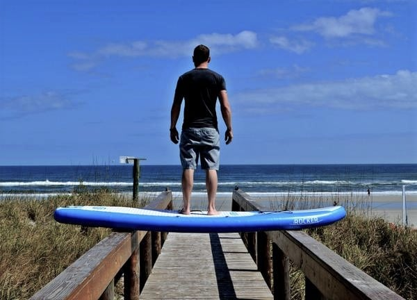 man standing on an inflatable paddle board that is laid across two sides of  a deck f048eac55d5a