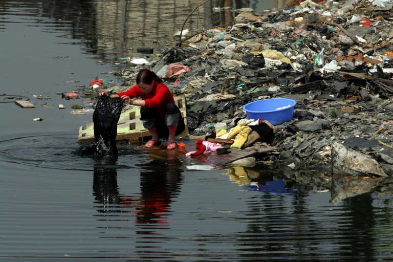 Woman Washing Clothes in Chinese River | Source: Greenpeace