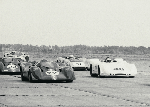 The parade lap at the 1970 12 Hours of Sebring. On the left is the NART Ferrari 312P Coupe of Mike Parkes and Chuck Parsons. The car finished 6th. On the right is the #48 Porsche 908/02 of Steve McQueen and Peter Revson. The car finished 2nd only 22 seconds behind the winning Ferrari. That is McQueen seen driving in this photo.